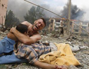 Photo of weeping man clutching dead body in urban wreckage in Gori in 2008.