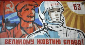 Soviet era propaganda poster showing astronaut and worker.