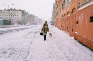 A warmly bundled woman walks her dog along a snowy street in Norilsk, Russia, at -32°C.