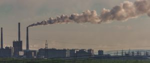 A gray photo shows a long plume of steam/smoke emanating from a high factory chimney in Norilsk, Russia.