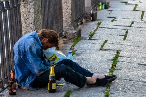 Photograph showing a drunk man, slumped on the sidewalk in St. Petersburg, Russia..