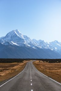 Photography of a long road approaching Mount Cook, New Zealand's highest peak.