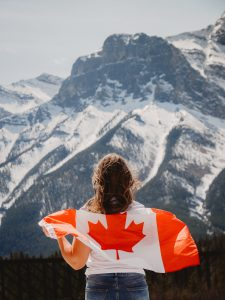 Photograph of Canadian woman and flag in front of snowy mountain in Alberta, Canada.
