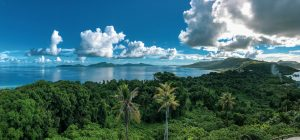 Photograph of Chuuk Lagoon in Micronesia, featuring blue sky with white clouds and blue water with adjacent green trees.