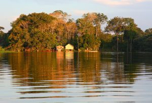 Photograph of small buildings along the broad Amazon River.